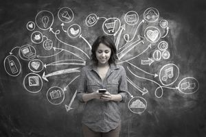 Girl on phone in front of backdrop of chalkboard with social media and online symbol sketches