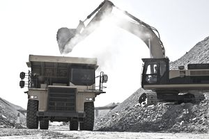 Digger loading truck in quarry for a construction project