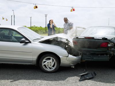Two upset men at an intersection after a car accident.