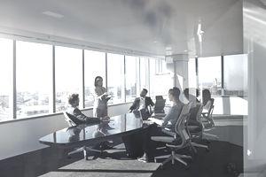 Young S Corporation owner pitching a project in a penthouse executive boardroom to investors.