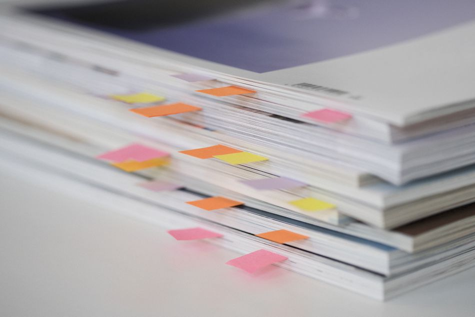 High angle view of stack of books with colorful bookmarks on table