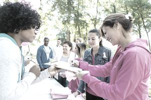 Diverse people registering for charity breast cancer awareness race