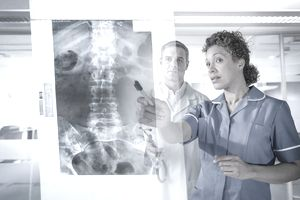 Two doctors reading an xray of a spine