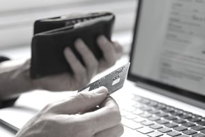 Person holding a credit card in one hand and a wallet in another in front of a laptop