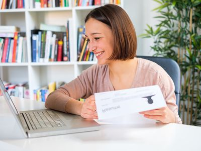 Woman looking at laptop and resume in hand
