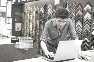 Owner of frame store using laptop computer