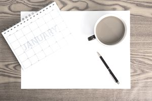 A blank editorial calendar on a desk with a pen and a cup of coffee.