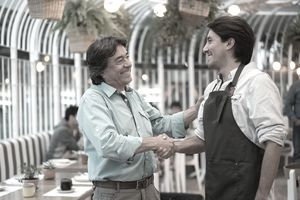 Two men, one in an apron, shaking hands at a single-unit franchise cafe