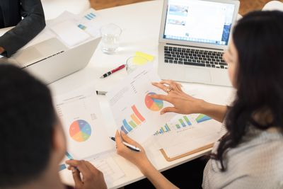 Businesswoman discussing pie charts at conference table meeting