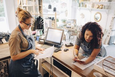 Two retail workers looking at sales reports in their store.