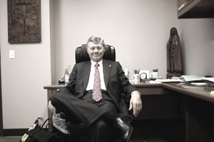 Tom Monaghan founder of Domino's Pizza, in his office with Catholic icons and statues