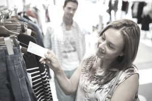 Woman checking tag while shopping in clothing store
