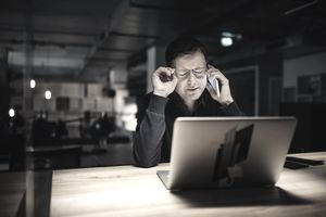 Frustrated businessman using phone while working late on laptop