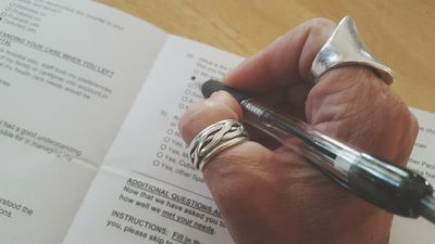 a person's hand filling out a survey