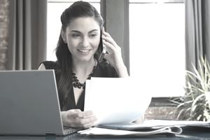 businesswoman talking on the phone with a manufacturer and using a script.
