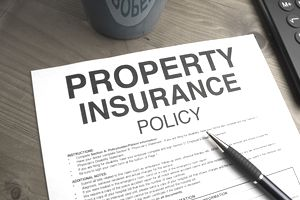 A property insurance policy for a commercial property on a table with a pen.