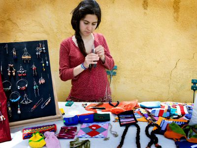 Woman selling jewlery at a craft fair.