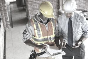 High angle view of tradesman and architect discussing work order at construction site