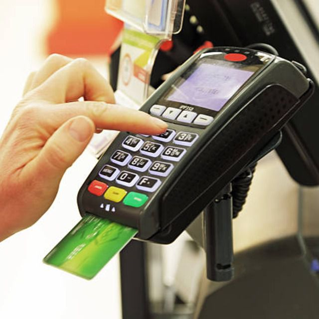 Customer inserting their credit card into a credit card reader in store