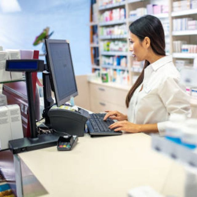 Pharmacist typing in prescription on keyboard of a computer at counter in drugstore