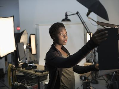 woman who owns a small photography business adjusting her lighting equipment.