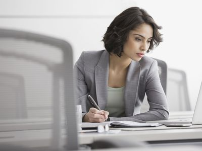 a woman writing in a notebook in a conference room