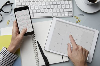 Hands using calendar apps being used on a phone and iPad