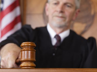 A judge banging a gavel in a courtroom.