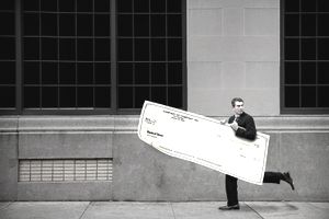 A man in a suit running down the street carrying an oversize business check indicating business fraud.