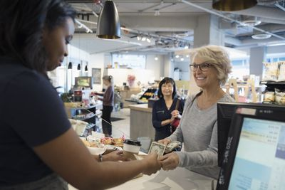 Smiling senior woman paying worker with cash at market checkout