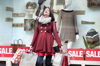 Woman holding several shopping bags and leaning against store window with sale signs
