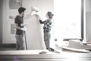 Couple choosing a paint color by holding up swatches to a wall