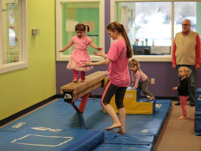 Little girl walking on a gymnastic balance beam at The Little Gym.