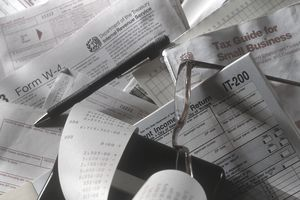 Business tax forms laying in a messy stack with a pen, calculator, and glasses