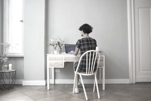 Back view of young woman sitting at desk at home using laptop