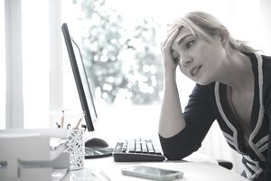 Frustrated Caucasian businesswoman using computer