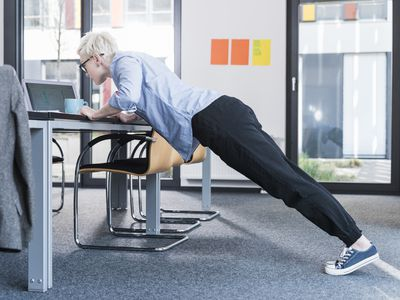 Businesswoman in office doing isometric exercises