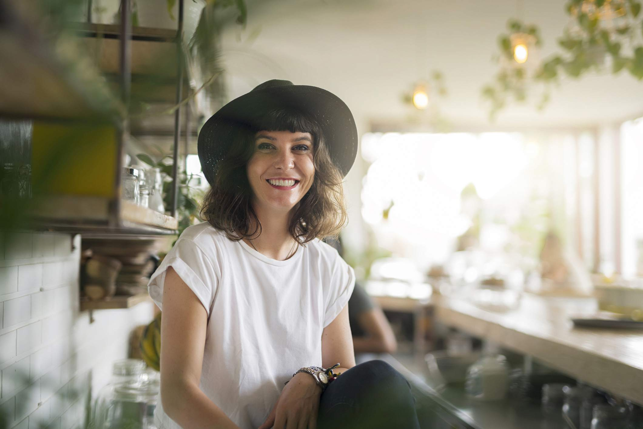 Portrait of woman with black hat behind the bar in a cafe