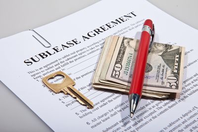 A sublease legal agreement with a key, pen and folded money