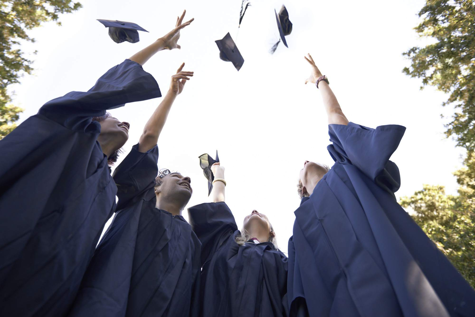 students throwing cap and tassels in the air at graduation
