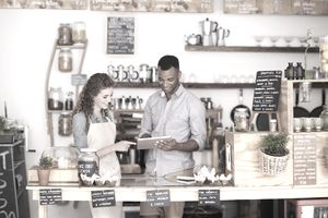 Cropped shop of a handsome coffee shop owner showing a waitress the ropes
