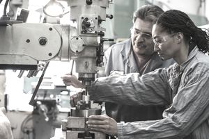 Workers using drill press in factory
