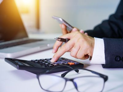 Hands of a suited male businessman working on calculator to avoid accounting mistakes