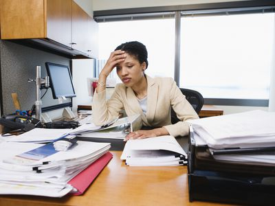 Businesswoman overwhelmed by work and time restraints in an office