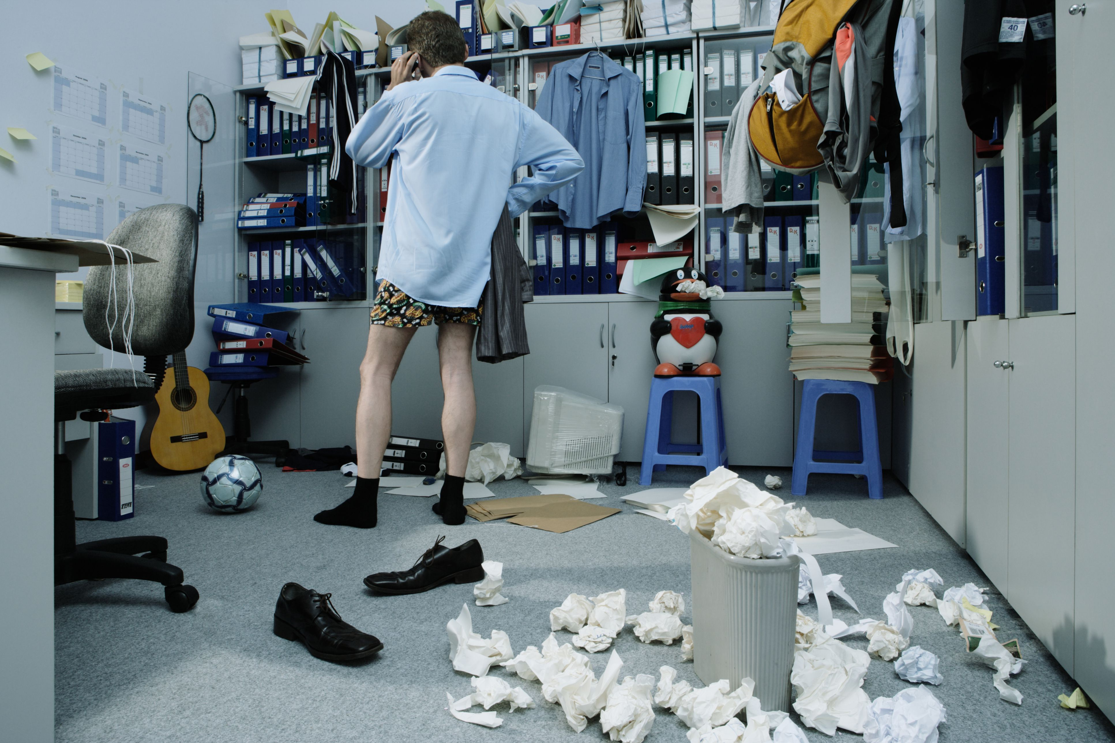 Man without pants on in messy office