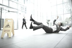 Businessman slipping on floor of office building