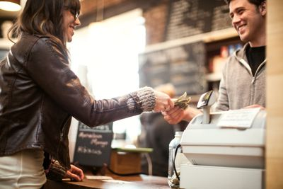 Customer paying business owner with cash