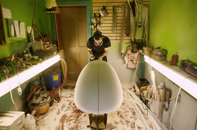 Shaper shapes a board at a Maine surf shop