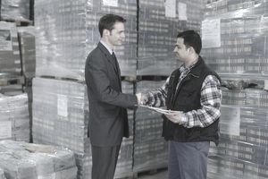 Men shaking hands in warehouse