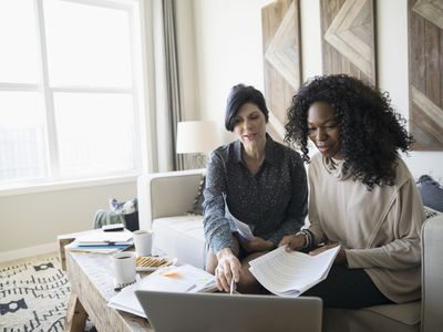 Two women with laptop and paperwork meeting in a living room